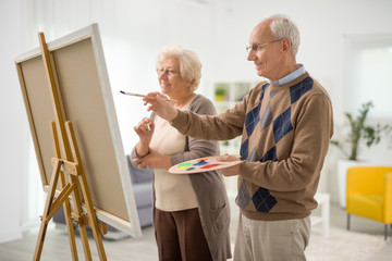 Older man and woman painting on canvas