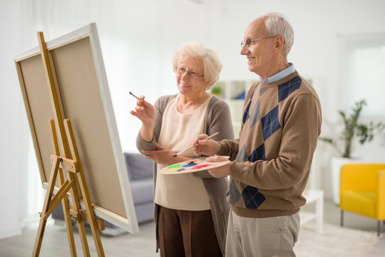 Senior couple drawing together on canvas