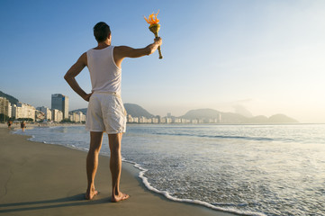 Athlete in old-fashioned white uniform standing with sport torch against Rio de Janeiro Brazil skyline at Copacabana Beach