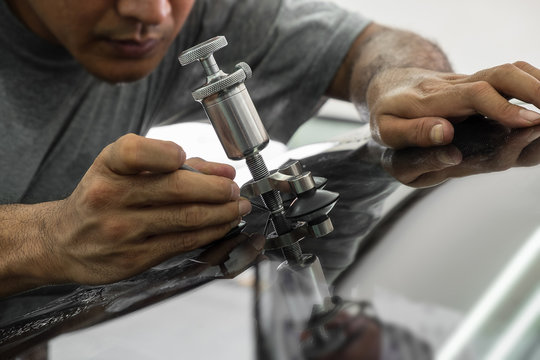 A man using repairing equipment to fix damaged windshield