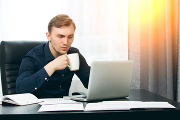 Casual dressed man ready to drink coffee while checking news