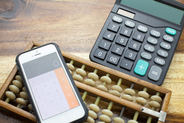 Smartphone,Abacus,calculator with wooden table background