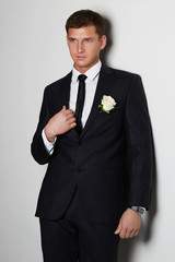 Handsome man with flower. young groom man in suit.elegant boy
