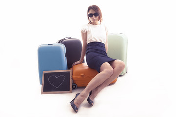 businesswoman waiting sitting over her suitcases