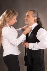 Frau hilft Mann mit Hemd und Krawatte