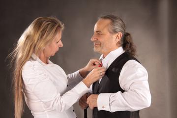 Frau hilft Mann beim Ankleiden