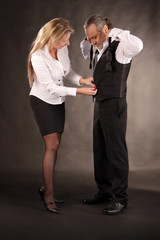 Mann lässt sich von Ehefrau helfen beim Anziehen