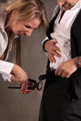 Frau mit Kneifzange am Hosenschlitz des Mannes