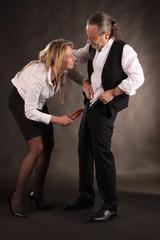 Frau zieht Reißverschluss von Mann mit Rohrzange