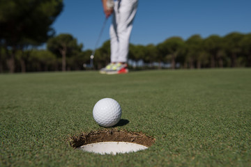 golf player hitting shot, ball on edge of hole