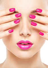 Close-up face of a beautiful  girl with  pink nails and lips.