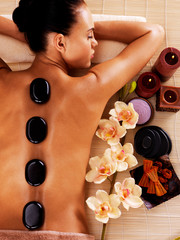 Adult woman relaxing in spa salon with hot stones on body