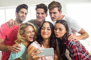 Friends making faces while taking selfie at home