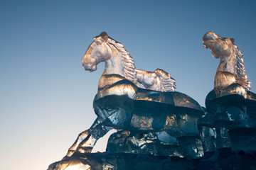 The intricately carved ice horses create a beautiful scene as the sun sets.