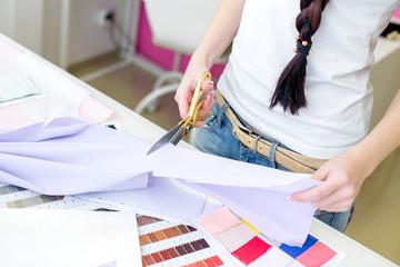 seamstress cuts fabric with scissors