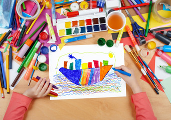 child drawing ocean liner ship, top view hands with pencil painting picture on paper, artwork workplace