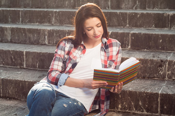 Young beautiful girl reading a book and resting on stairs