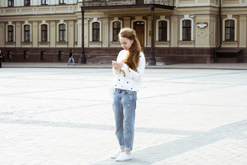 Young beautiful long-haired hipster girl on a sunny day outdoors. Lifestyle portrait of a trendy woman using cellphone walking in the city. Concept of freedom and happiness.