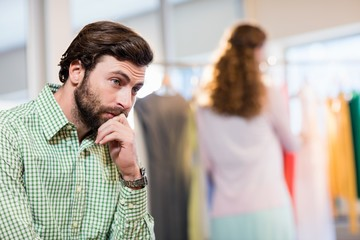 Bored man waiting his wife while woman by clothes rack