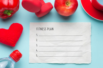 Fitness plan concept. View from above. Nutrition diet and fitness workout routine. Healthy red fruits, water and dumbbells for slimming down concept.