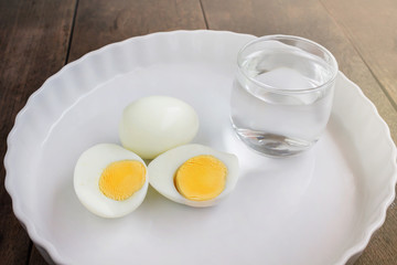Boil eggs on white plate with glass of water in morning meal fee