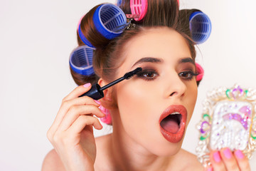 Young girl doing makeup and hairstyle using curlers