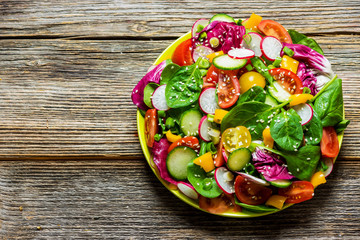 Wall Mural - Fresh vegetable salad on wooden background