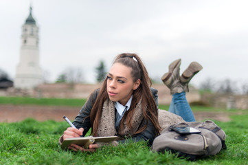 Beautiful girl writing in a book / Girl student in park writes in writing book
