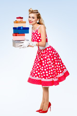 Full body of woman in pin-up style red dress with gift boxes