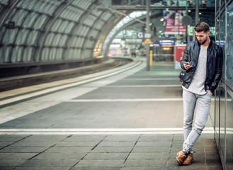Junger Mann mit Smartphone im Bahnhof Wall mural