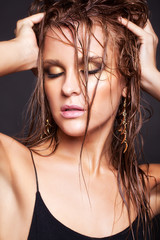 Woman with wet shining  makeup and closed eyes on black backgrou