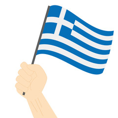 Hand holding and raising the national flag of Greece