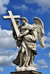 Angel with the Holy Cross and beautiful sky, Marble statue from Sant'Angelo bridge monumental balustrade in the center of Rome
