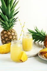Bottles of pineapple juice on a white wooden table
