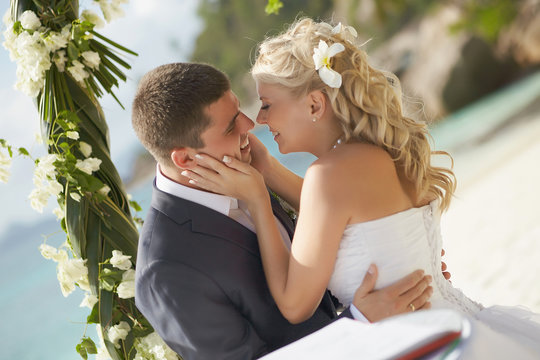 Couple kissing during wedding registry ceremony on tropical isla