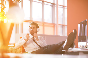 relaxed young businessman first at workplace at early morning