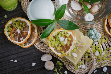Composition of spa treatment with green salt and soap on wooden