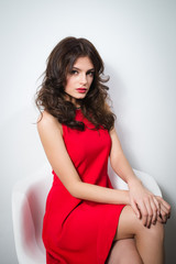 young gorgeous woman in red dress sitting on a chair with hands on her knees