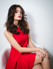 young beautiful woman in red dress sitting on a chair with hands on her knees