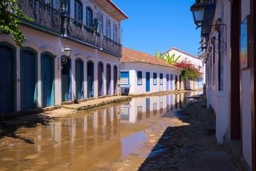 Casas no centro histórico de Paraty com rua alagada pela elevação da maré