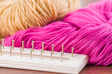 Closeup brown and pink yarn balls lying next to wodden knitting tool board with nails