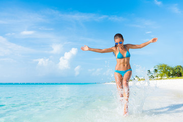 Freedom carefree girl playing splashing water having fun on tropical beach vacation getaway travel holiday destination. Playful woman with abs slim bikini body relaxing feeling free.