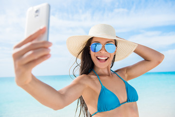 Selfie smartphone girl taking mobile phone photo on beach vacation during summer travel holidays. Sexy young bikini woman wearing fashion mirrored aviator sunglasses posing for camera having fun.