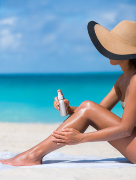 Sunscreen suntan lotion spray skincare product closeup of woman putting tanning oil on legs. Hand holding sunblock or mosquito repellent bottle spraying on body sunbathing at beach summer vacation.