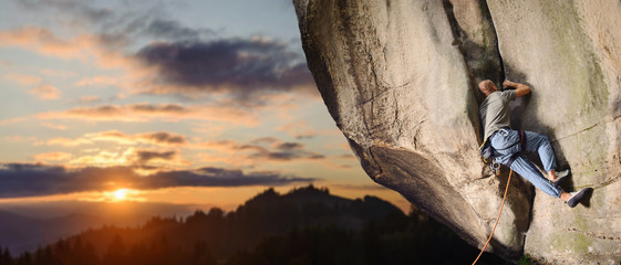Young man rock climber climbing challenging route on rocky wall against scenic sunset background. Summer time. Climbing equipment. Panoramic picture