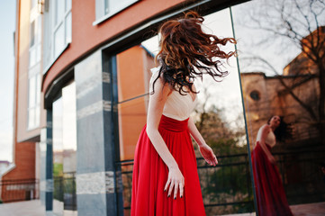 Portrait of fashionable girl at red evening dress with hair in t