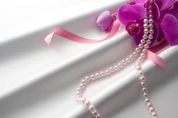 白色のサテンとピンク色の胡蝶蘭とリボンとパール