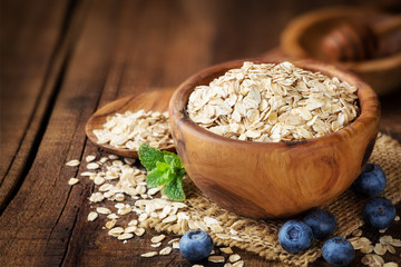 Rolled oats in a wooden bowl with fresh blueberries, sprig of mint and honey at the background