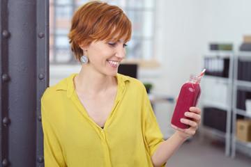 moderne frau im büro hält einen smoothie in der hand