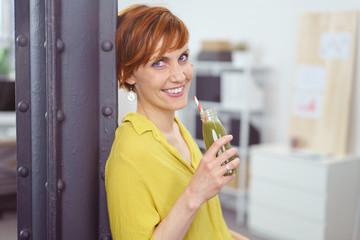 frau macht eine pause im büro und trinkt einen grünen smoothie